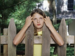 Girl Waiting Behind Fence of House
